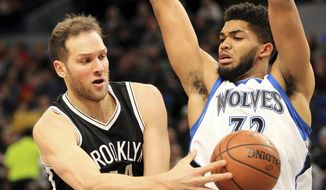 Minnesota Timberwolves center Karl-Anthony Towns (32) defends on a pass from Brooklyn Nets forward Bojan Bogdanovic (44) during the first quarter of an NBA basketball in Minneapolis, Saturday, Jan. 28, 2017. (AP Photo/Andy Clayton-King)