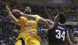 Texas A&M center Tyler Davis (34) fouls West Virginia forward Esa Ahmad (23) as he drives to the basket during the second half of an NCAA college basketball game, Saturday, Jan. 28, 2017, in Morgantown, W.Va. (AP Photo/Raymond Thompson)