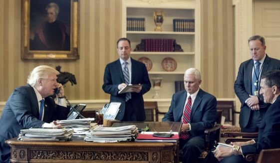 President Donald Trump, accompanied by, from second from left, Chief of Staff Reince Priebus, Vice President Mike Pence, White House press secretary Sean Spicer and National Security Adviser Michael Flynn, speaks on the phone with with Russian President Vladimir Putin, Saturday, Jan. 28, 2017, in the Oval Office at the White House in Washington. (AP Photo/Andrew Harnik)