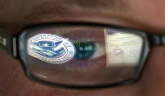 A reflection of the Department of Homeland Security logo is seen in the glasses of a cyber security analyst in the watch and warning center at the Department of Homeland Security's secretive cyber defense facility at Idaho National Laboratory in Idaho Falls, Idaho, on Sept. 30, 2011. (Associated Press) **FILE**