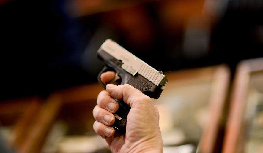 a woman holds a small pistol at the Annapolis Gun Show, Annapolis, Md., Sunday, April 14, 2013. (Andrew Harnik/The Washington Times)