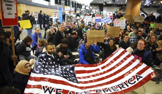 "Demonstrators sit down in the concourse and hold a sign that reads ""We are America,"" as more than 1,000 people gather at Seattle-Tacoma International Airport, to protest President Donald Trump's order that restricts immigration to the U.S., Saturday, Jan. 28, 2017, in Seattle. President Trump signed an executive order Friday that bans legal U.S. residents and visa-holders from seven Muslim-majority nations from entering the U.S. for 90 days and puts an indefinite hold on a program resettling Syrian refugees. (Genna Martin/seattlepi.com via AP)"