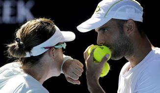 Abigail Speers of the US and Juan Sebastian Cabal of Colombia talk tactics in their mixed doubles' final against India's Sania Mirza and Ivan Dodig at the Australian Open tennis championships in Melbourne, Australia, Sunday, Jan. 29, 2017. (AP Photo/Aaron Favila)