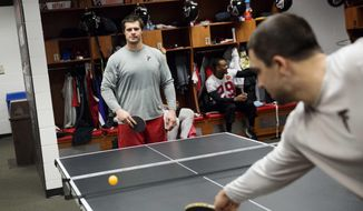 In this Thursday, Jan. 26, 2017 photo, Atlanta Falcons' Andy Levitre, left, plays against teammate Josh Harris in a game of pingpong in the locker room at the NFL football team's practice facility in Flowery Branch, Ga. For the Super Bowl-bound Falcons, brotherhood begins at three pingpong tables in the middle of their locker room. That's where friendships are forged, friendly wagers settled and the competitive juices really get flowing. (AP Photo/David Goldman)