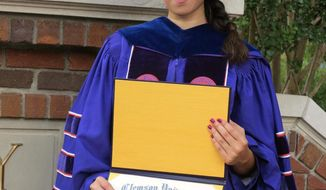 In an undated photo provided by Parastoo Amiri, Nazanin Zinouri poses for a photo with her PHD degree from Clemson University. Zinouri has a visa and has lived in the U.S. since August 2010. On Jan 20, 2017, Zinouri flew to Iran, expecting to have three weeks of family time with her mother, brother and sister. Instead, she was barely in Tehran before she began trying to get home to South Carolina. (Parastoo Amiri via AP)