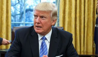 President Trump waits for more executive orders to sign, resulting in a frenzy of outrage among Democrats, the news media and Hollywood. (Associated Press)
