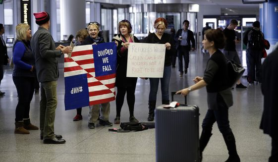 Demonstrators hold signs at San Francisco International Airport in protest of President Donald Trump's executive order that bars citizens of seven predominantly Muslim-majority countries from entering the U.S. Monday, Jan. 30, 2017, in San Francisco. (AP Photo/Marcio Jose Sanchez)