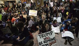 Jacklyn Parsons, center raises her fist in the air while participating in a sit-in protest at the Albuquerque Sunport Sunday, Jan. 29, 2017, in Albuquerque, N.M.. A group of 1,000 protesters took over the arrival and departure area to express their opposition to President Trump's Executive Order to ban entry to the U.S to citizens from 7 predominant muslim countries,  (Adolphe Pierre-Louis/Albuquerque Journal)