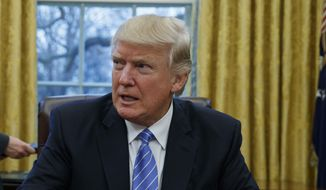 President Donald Trump sits at his desk in the Oval Office of the White House in Washington in this Jan. 23, 2017, file photo. (AP Photo/Evan Vucci, File)