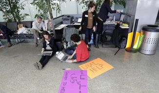 Attorneys offer legal help near the arrivals gate at San Francisco International Airport following President Donald Trump's executive order that bars citizens of seven predominantly Muslim-majority countries from entering the U.S. Monday, Jan. 30, 2017, in San Francisco. (AP Photo/Marcio Jose Sanchez)
