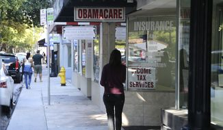 """A woman walks past a sign advertising """"Obamacare"""", Tuesday, Jan. 31, 2017, in Miami. The enrollment period for the federal health care law known as """"Obamacare"""" ends at the end of the day Tuesday. The Republican-lead Senate has passed a measure to take the first step forward on dismantling President Barack Obama's health care law. (AP Photo/Lynne Sladky) **FILE**"""