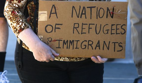 A protestor holds a sign in support of refugees as she prepares to join a march around the Quad at the University of Alabama, in Tuscaloosa, Ala., to express their discontent with President Donald Trump's executive order halting some immigrants from entering the United States Tuesday, Jan. 31, 2017. (AP Photo/Gary Cosby Jr., Tuscaloosa News)