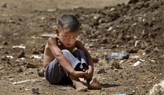 A Syrian refugee boy sits on the ground at a temporary refugee camp, in the eastern Lebanese town of Al-Faour, Bekaa valley near the Syria-Lebanon border in this Sept. 11, 2013, file photo. On Tuesday, Jan. 31, 2017, UNICEF appealed for $3.3 billion this year to help millions of children worldwide facing conflict, malnutrition and other humanitarian emergencies. (AP Photo/Hussein Malla, File)