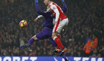 Arsenal's Laurent Koscielny, front, and Watford's goalkeeper Heurelho Gomes challenge for the ball during the English Premier League soccer match between Arsenal and Watford at the Emirates stadium in London, Tuesday, Jan. 31, 2017.(AP Photo/Frank Augstein)