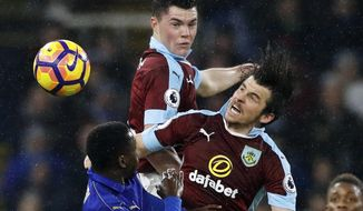 Burnley's Joey Barton, right,  and Michael Keane, centre battle for the ball in the air with Leicester City's Wilfred Ndidi during the English Premier League soccer match between Burnley and Leicester City, at Turf Moor, in Burnley., England, Tuesday Jan. 31, 2017. (Martin Rickett/PA via AP)
