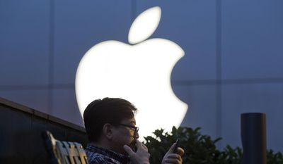 FILE - In this Friday, May 13, 2016, file photo, a man uses his mobile phone near an Apple store in Beijing, China. Apple Inc. reports financial results Tuesday, Jan. 31, 2017. (AP Photo/Ng Han Guan, File)