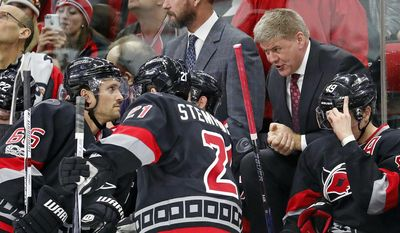 Carolina Hurricanes head coach Bill Peters speaks to Ron Hainsey (65) and Lee Stempniak (21) during a timeout in the second period of an NHL hockey game against the Philadelphia Flyers, Tuesday, Jan. 31, 2017, in Raleigh, N.C. (AP Photo/Karl B DeBlaker)