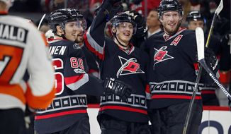 Carolina Hurricanes' Sebastian Aho (20) center, celebrates his first career hat trick goal with teammates Jordan Staal (11), Teuvo Teravainen (86) and Justin Faulk, during the second period of an NHL hockey game against the Philadelphia Flyers, Tuesday, Jan. 31, 2017, in Raleigh, N.C. (AP Photo/Karl B DeBlaker)