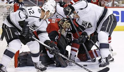 Los Angeles Kings right wing Dustin Brown, right, and right wing Marian Gaborik (12) try to shoot the puck at Arizona Coyotes goalie Mike Smith (41) during the first period of an NHL hockey game, Tuesday, Jan. 31, 2017, in Glendale, Ariz. (AP Photo/Ross D. Franklin)