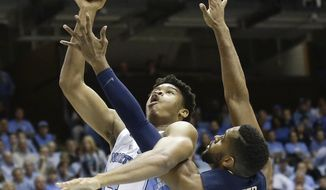 North Carolina's Isaiah Hicks (4) shoots while Pittsburgh's Sheldon Jeter (21) defends during the first half of an NCAA college basketball game in Chapel Hill, N.C., Tuesday, Jan. 31, 2017. (AP Photo/Gerry Broome)