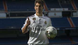 FILE - In this Monday, Jan. 26, 2015 file photo, Brazil international soccer player Lucas Silva poses with the ball during his official presentation at the Santiago Bernabeu stadium in Madrid, Spain after signing for Real Madrid. With Real Madrid and Atletico Madrid banned from registering new players and Barcelona not looking to make any blockbuster additions to its squad, the final day of the transfer window in Spain was marked by low-key transactions involving smaller clubs. Madrid, which along with Atletico was sanctioned by FIFA for violating transfer rules while signing underage players, made the lone move of sending defensive midfielder Lucas Silva on a loan to former club Cruzeiro in Brazil, it was reported on Tuesday, Jan. 31, 2017. (AP Photo/Andres Kudacki, File)