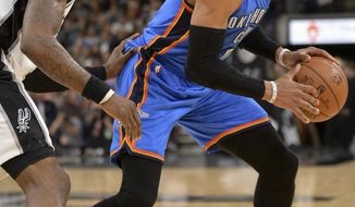 Oklahoma City Thunder guard Russell Westbrook, right, evades San Antonio Spurs forward Jonathon Simmons during the first half of an NBA basketball game, Tuesday, Jan. 31, 2017, in San Antonio. (AP Photo/Darren Abate)