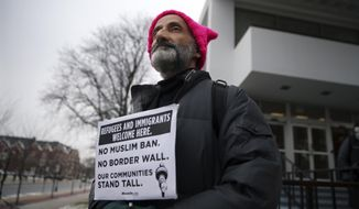 Rutgers University math professor Shadi Tahvildar-Zadeh, holds a sign as Rutgers University students and supporters gather to express their discontent with President Donald Trump's executive order halting some immigrants from entering the United States Tuesday, Jan. 31, 2017, in New Brunswick, N.J. (AP Photo/Mel Evans)