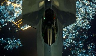 In this Friday, Sept. 26, 2014 photo, released by the U.S. Air Force, a U.S Air Force KC-10 Extender refuels an F-22 Raptor fighter aircraft prior to strike operations in Syria. The F-22s, making their combat debut, were part of a strike package that was engaging Islamic State group targets in Syria. (AP Photo/U.S. Air Force, Russ Scalf )