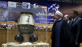 In this photo released by official website of the office of the Iranian Presidency, President Hassan Rouhani, left, visits an exhibition of Iran's latest achievements of space technology, in Tehran, Iran, Wednesday, Feb. 1, 2017. President Hassan Rouhani has lashed out at the recent executive order by U.S. president Donald Trump to suspend immigration and visa processes for nationals from seven majority-Muslim countries, including Iran. Minister of Communications and Information Technology Mahmoud Vaezi, right, accompanies Rouhani. (Iranian Presidency Office via AP)