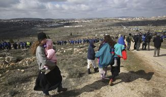 Settler kids walk outside the West Bank outpost of Amona, Wednesday, Feb. 1, 2017. Israeli forces have begun evacuating a controversial settlement  Amona, which is the largest of about 100 unauthorized outposts erected in the West Bank without permission but generally tolerated by the Israeli government. (AP Photo/Oded Balilty)