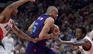 Charlotte Hornets guard Nicolas Batum, center, dribbles past Portland Trail Blazers forward Maurice Harkless, left, and forward Al-Farouq Aminu, right, during the first half of an NBA basketball game in Portland, Ore., Tuesday, Jan. 31, 2017. (AP Photo/Craig Mitchelldyer)