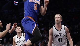 New York Knicks' Kristaps Porzingis (6), of Latvia, drives past Brooklyn Nets' Justin Hamilton (41) during the first half of an NBA basketball game Wednesday, Feb. 1, 2017, in New York. (AP Photo/Frank Franklin II)
