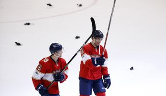 Florida Panthers defenseman Michael Matheson (19) and center Greg McKegg (41) celebrate as fans throw plastic rats onto the ice after the Panthers defeated the Ottawa Senators 6-5 in an NHL hockey game, Tuesday, Jan. 31, 2017, in Sunrise, Fla. (AP Photo/Wilfredo Lee)