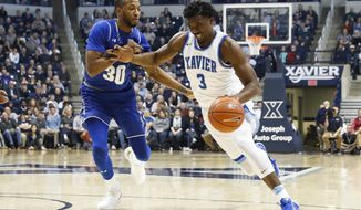 Xavier's Quentin Goodin (3) drives around Seton Hall's Madison Jones (30) during the first half of an NCAA college basketball game, Wednesday, Feb. 1, 2017, in Cincinnati. (AP Photo/John Minchillo)