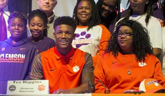 Oak Ridge High School wide receiver Tee Higgins, surrounded by family and friends, looks on during a national singing day in Knoxville, Tenn., Wednesday, Feb. 1, 2017. Higgins committed to Clemson University. (Brianna Paciorka/Knoxville News Sentinel via AP)
