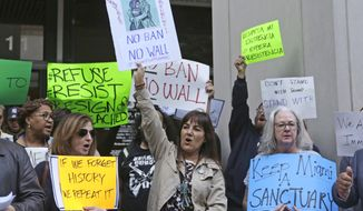 Protesters chant slogans against President Donald Trump and Miami-Dade County Mayor Carlos Gimenez in downtown Miami, Tuesday, Jan. 31, 2017. Gimenez issued a controversial order last week assuring the Trump administration that Miami-Dade is not functioning as a sanctuary city for illegal immigrants. (AP Photo/Alan Diaz)