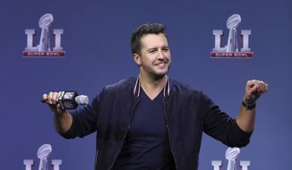 "Singer Luke Bryan, who will perform the national anthem, does his version of the Atlanta Falcons ""Dirty Bird"" dance while answering a question during an NFL football news conference about the pregame show for Super Bowl 51, Thursday, Feb. 2, 2017, in Houston. (Curtis Compton/Atlanta Journal-Constitution via AP)"
