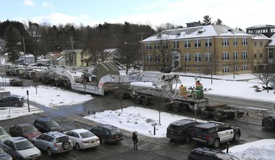 In this Feb. 1, 2017 photo provided by Ken Chapman, of Morrisville State College, a 175-ton steam turbine moves down a street aboard a large flatbed in Morrisville, N.Y. The turbine was made at General Electric's Schenectady N.Y. plant and is slowly making its way across the central section of the state while headed to Pennsylvania. (Ken Chapman/Morrisville State College via AP)