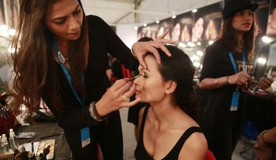 In this Feb. 1, 2017 photo, a makeup artist applies eye-shadow on Anjali Lama, a transgender model from Nepal, during Lakme Fashion week in Mumbai, India. Growing up as the fifth son in a poor farming family in rural Nepal the dream to be a fashion model came late in life. First came a long, painful struggle to accept that he felt deeply female. It was a chance encounter with a group of transgender women that turned Lama's life around by putting her in touch with the Blue Diamond Society, an advocacy group for Nepal's LGBT community. In 2005 she came out to her friends and family as a transgender woman. (AP Photo/Rafiq Maqbool)