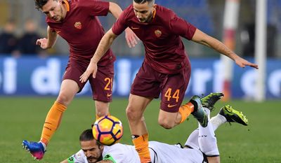 Roma's Kostas Manolas, foreground, and Mario Rui, left, and Cesena's Alejandro Rodriguez vie for the ball during the Italians Cup quarterfinal soccer match between Roma and Cesena at the Olympic stadium in Rome, Wednesday, Feb. 1, 2017. (Ettore Ferrari/ANSA via AP)