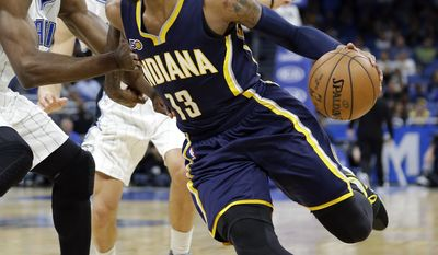 Indiana Pacers' Paul George (13) drives around Orlando Magic's Serge Ibaka, left, and Aaron Gordon, center, during the first half of an NBA basketball game, Wednesday, Feb. 1, 2017, in Orlando, Fla. (AP Photo/John Raoux)