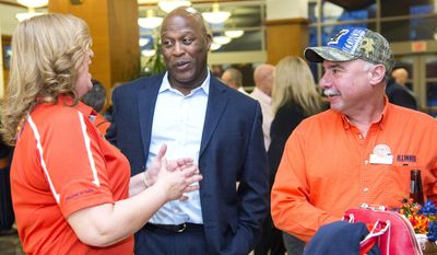 Illinois football coach Lovie Smith, center, chats with Denise and Mark Dalton during a reception with members of the Quarterback Club on football signing day, Wednesday, Feb. 1, 2017, in Urbana, Ill. (Robin Scholz/The News Gazette via AP)