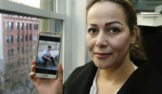 Reema Duhman poses for a photo Wednesday, Feb. 1, 2017, in the offices of the Northwest Immigrant Rights Project in Seattle with a photo of her son displayed on her phone. Duhman, who fled war-torn Syria and now is a lawful permanent U.S. resident who lives in Seattle, had almost completed the complicated process of securing a visa for her 16-year-old son, who is still in Syria, when President Donald Trump issued an executive order prohibiting anyone from Syria and six other countries from traveling to the U.S. Duhman is a plaintiff in a federal class-action lawsuit filed this week by the Northwest Immigrant Rights Project that says Trump's order is unconstitutional and a violation of the Immigration and Nationality Act. (AP Photo/Ted S. Warren)