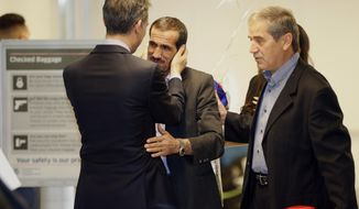 Los Angeles Mayor Eric Garcetti, left, hugs Ali Vayeghan, an Iranian citizen with a valid U.S. visa, middle, as he is welcomed by his brother Houssein Vayghan at Los Angeles International Airport Thursday, Feb. 2, 2017. An Iranian man turned away from Los Angeles International Airport under President Donald Trump's executive order barring people from seven Muslim-majority nations has arrived back in the U.S. under a federal judge's order. (AP Photo/Damian Dovarganes)