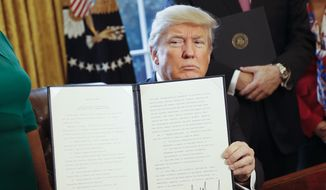 President Donald Trump holds up an executive order after his signing the order in the Oval Office of the White House in Washington on Feb. 3, 2017. The executive order that will direct the Treasury secretary to review the 2010 Dodd-Frank financial oversight law, which reshaped financial regulation after 2008-2009 crisis. (Associated Press) **FILE**