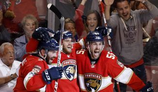 Florida Panthers left wing Jonathan Huberdeau, center, celebrates with defenseman Keith Yandle, left, and defenseman Jason Demers after Huberdeau scored during the second period of an NHL hockey game against the Anaheim Ducks, Friday, Feb. 3, 2017, in Sunrise, Fla. (AP Photo/Wilfredo Lee)