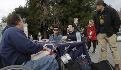 University of California, Berkeley, student Bradley Devlin, center, sits with others at a Berkeley College Republicans table on campus in Berkeley, Calif., Thursday, Feb. 2, 2017. Chaos that erupted at the university to oppose right-wing provocateur Milo Yiannopoulos was shocking not just for the images of protesters setting fires, smashing windows and hurling explosives at police, but because of where it took place. (AP Photo/Jeff Chiu)