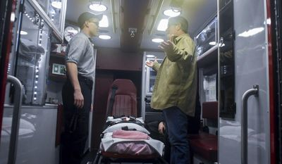 CORRECTS SOURCE TO THE REPUBLICAN-HERALD, NOT THE TIMES & TRIBUNE-Bill Malloy, right, meets with first responders on Thursday, Jan. 19, 2017 who came to the rescue after he suffered a heart attack in Valley View, Pa. Tyler Perry, left, 19, EMT student, helped to calm his wife while the others worked on him. Perry showed Malloy the ambulance that took him to the hospital. (Andy Matsko/Republican-Herald via AP)