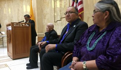 Guests of honor Darlene Arviso, far right, of the Navajo Nation and Robert Taken Alive of the Standing Rock Sioux tribe visit the New Mexico Statehouse in Santa Fe as guests of honor on Friday, Feb. 3, 2017. Local Native American leaders signed a letter to President Donald Trump expressing solidarity with the Standing Rock Sioux and other opponents of the Dakota Access oil pipeline project. The annual Native American day in the state capital focused on water issues and recognized Arviso her work delivering water free of charge to rural residents without access to running water. (AP Photo/Morgan Lee)