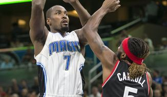 Orlando Magic center Bismack Biyombo (11) shoots over Toronto Raptors forward DeMarre Carroll (5) during the first half of an NBA basketball game in Orlando, Fla., Friday, Feb. 3, 2017. (AP Photo/Willie J. Allen Jr.)